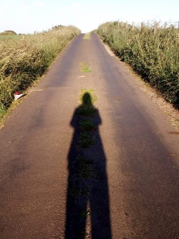 a shadow image of the author in the middle of a lane on the summer solstice